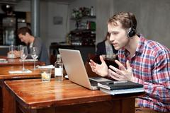 Young man wearing headphones using laptop in cafe Kuvituskuvat