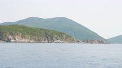 View from moving boat on coastline with woody mountain in the background - stock footage