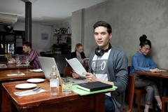 Young man with laptop in cafe Stock Photos