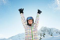 Portrait of teenage girl skier with arms raised, Les Arcs, Haute-Savoie, France - stock photo