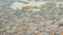 Stones under the waving sea water - stock footage