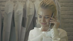 Female sales Assistant in bridalwear store with Smart Phone Stock Footage