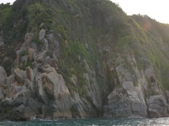 Rocky landscape on a sea coast panning from left to right. View from moving boat Stock Footage