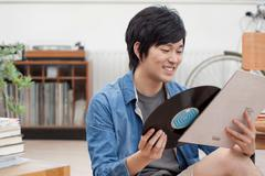 Portrait of young man holding vinyl record Kuvituskuvat