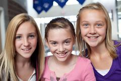 Close up portrait of three teen and pre-adolescent girls smiling - stock photo