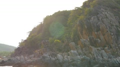 Rocky shore with trees in rays of sun. Panoramic view from moving boat - stock footage