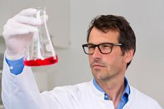 Male scientist examining ph-reaction of liquid in flask Stock Photos