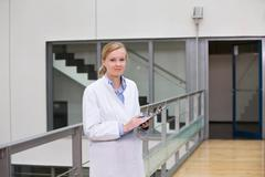 Female scientist in atrium with clipboard - stock photo