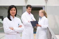 Group of  scientists in atrium with clipboard - stock photo