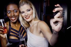 Two female friends making self portrait in nightclub Stock Photos