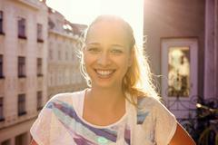 Portrait of young woman standing on city apartment balcony Stock Photos