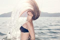 Young woman in sea throwing head back Stock Photos