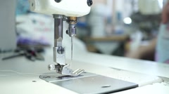 Factory seamstress at work and industrial sewing machine - stock footage