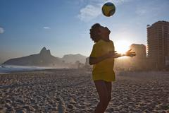 Young man heading football, Ipanema Beach, Rio, Brazil - stock photo