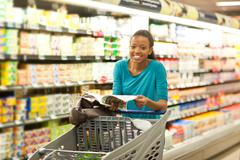 Female shopper with brochure in supermarket Stock Photos