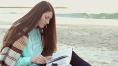 Young Woman Reading a Book and drinking hot tea near sea Stock Footage