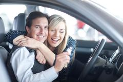 Couple sitting in new car with key in showroom Kuvituskuvat