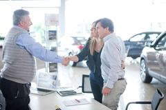 Car salesman and couple shaking hands in car showroom Stock Photos