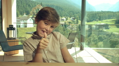 Happy boy looking camera ok sign saying hello in the mountains at home Stock Footage