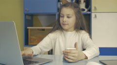Smart Kids. Small Schoolgirl is Sitting at the Desk and using Laptop Stock Footage
