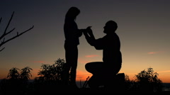 Man surprises his girlfriend with marriage proposal during sunset, super slow  Stock Footage