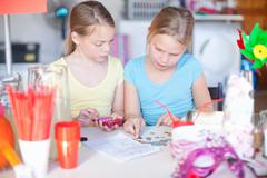 Two young sisters checking stall profits Stock Photos