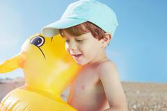 Boy hugging duck shaped float - stock photo