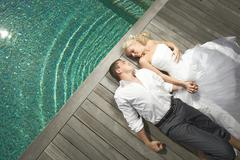 Beautiful young couple lying near pool with mind waves. Stock Photos