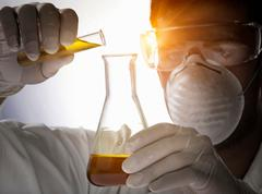 Close up of scientist pouring liquid into flask - stock photo