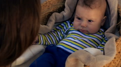Mother playing with her baby son in basket, super slow motion 240fps Stock Footage
