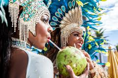 Samba dancers in costume, drinking coconut drinks, Ipanema Beach, Rio De Kuvituskuvat