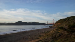 Evening time lapse of people leaving the beach by the Golden Gate Bridge Stock Footage