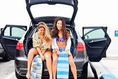 Female friends sitting in car boot with skateboards Stock Photos