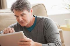 Mature man using digital tablet - stock photo