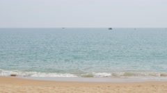 Sandy sea shore, calm water and boats on the horizon Stock Footage