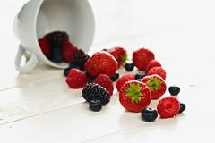 Strawberries, raspberries, blackberries and blueberries spilling form teacup Stock Photos