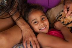 Girl lying with head in mother's lap - stock photo