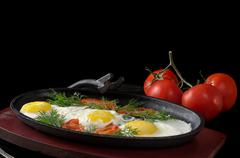 Scrambled eggs with tomatoes and whole tomatoes, on a black background Stock Photos