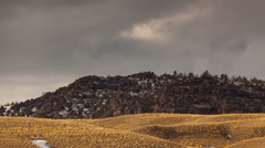 Timelapse clouds passing over rocky outcrop and winter grass - stock footage