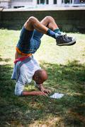 Young man doing handstand using tablet - stock photo