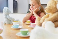 Girl having tea party with soft toys - stock photo