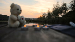 Candles and bear on the lake dock Stock Footage