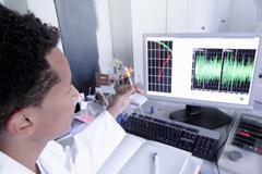 Scientist wearing lab coat working on computer Stock Photos