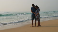 Happy couple expecting baby on a beach. Young man caressing laughing woman's - stock footage
