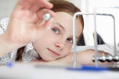 Girl playing with newton's cradle on desk Stock Photos