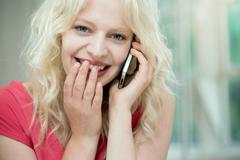 Young woman on cellphone, giggling - stock photo
