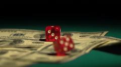Red dice falling on money, gambler playing game at casino, addiction to gambling Stock Footage