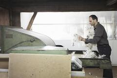 Man adding fleece to machine in wool factory Stock Photos