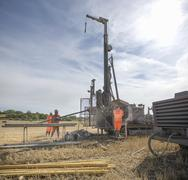 Small team of workers operating drilling rig in field Stock Photos