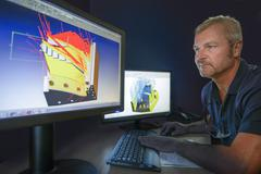 Engineer looking at computer monitor with Computer Aided Design diagrams Stock Photos